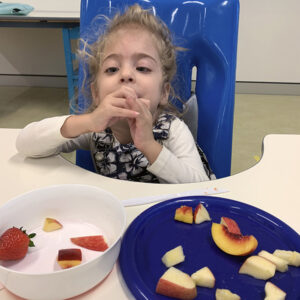 young girl sitting tryin stawberry and apple