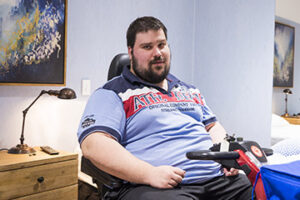 Man in wheelchair looking at camera. he is in a bedroom.