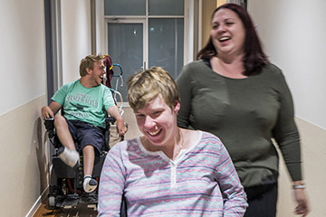 A staff member laughs with a client while pushing their wheelchair