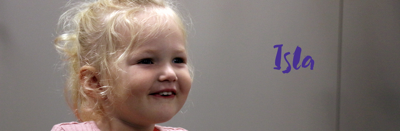 A three year old girl is smiling. Her name is Isla.