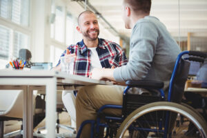 A man in a wheelchair talks to another man. They are in an office.